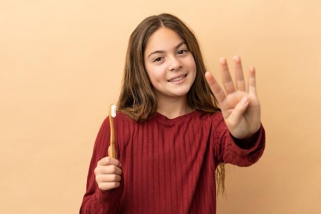 幸せなベージュの背景に分離された彼女の歯を磨いて、指で4を数える白人の少女