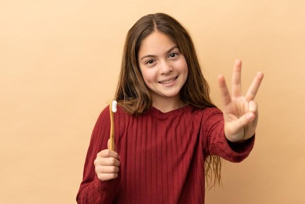 幸せなベージュの背景に分離された彼女の歯を磨き、指で3を数える白人の少女