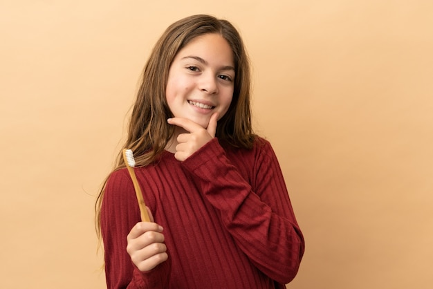 幸せと笑顔のベージュの背景に分離された彼女の歯を磨く白人の少女
