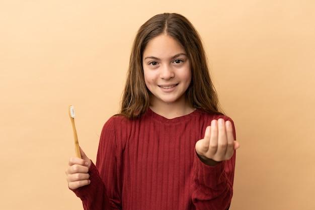 Маленькая кавказская девушка чистит зубы щеткой, изолированной на бежевом фоне, приглашая прийти с рукой. счастлив что ты пришел
