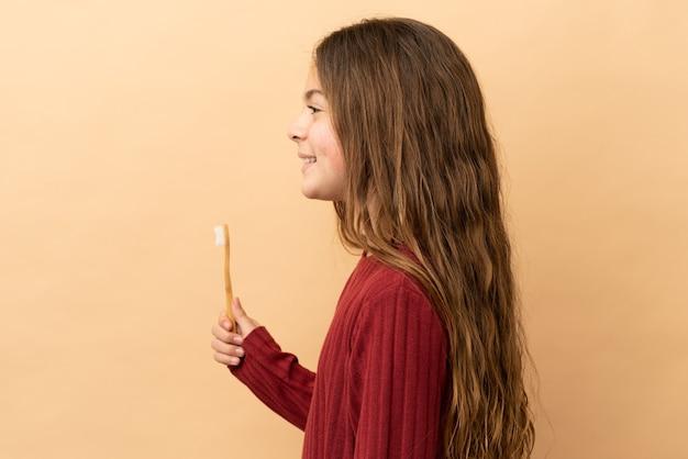 横向きの位置で笑っているベージュの背景に分離された彼女の歯を磨く白人の少女
