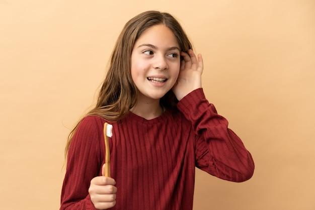 Маленькая кавказская девочка чистит зубы на бежевом фоне, слушая что-то, положив руку на ухо