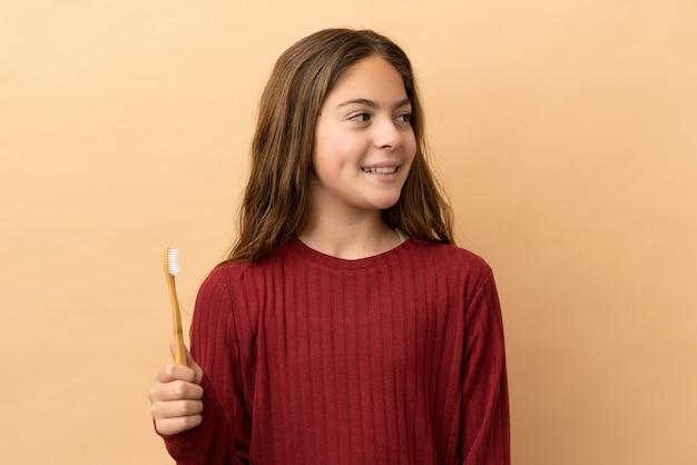 横を見て笑っているベージュの背景に分離された彼女の歯を磨く白人の少女