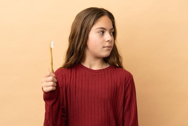 横を向いているベージュの背景に分離された彼女の歯を磨く白人の少女