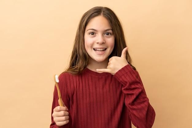 電話のジェスチャーを作るベージュの背景に分離された彼女の歯を磨く白人の少女。コールバックサイン