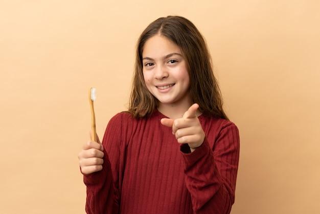 幸せな表情で正面を向いているベージュの背景に分離された彼女の歯を磨く白人の少女