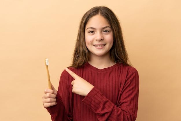 製品を提示するために側面を指しているベージュの背景に分離された彼女の歯を磨く白人の少女