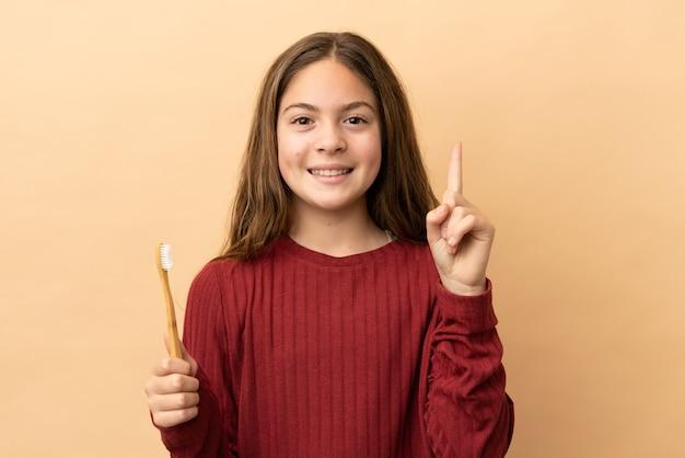 좋은 아이디어를 가리키는 베이지색 배경에 고립 된 그녀의 양치질 하는 백인 소녀