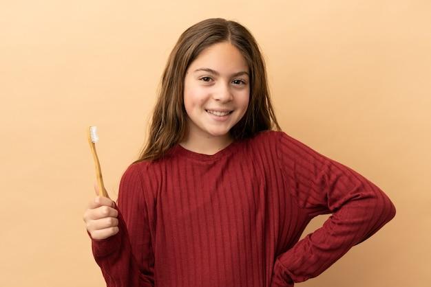 小さな白人の女の子が腰に腕を持ってポーズをとって笑顔でベージュの背景に分離された彼女の歯を磨く