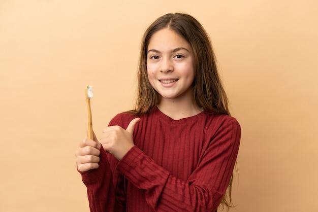 誇らしげで自己満足のベージュの背景に分離された彼女の歯を磨く白人の少女