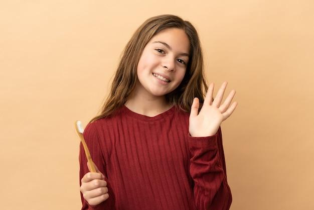 幸せな表情で手で敬礼するベージュの背景で隔離の彼女の歯を磨く白人の少女