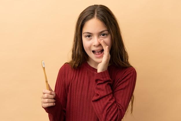 Маленькая кавказская девочка чистит зубы на бежевом фоне и кричит с широко открытым ртом