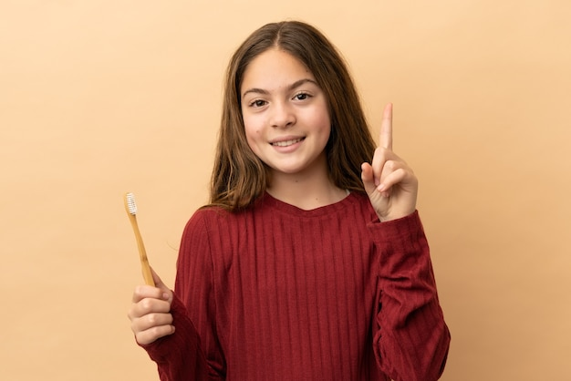 ベージュの背景で隔離された彼女の歯を磨く小さな白人の女の子は、最高の兆候を示して指を持ち上げます