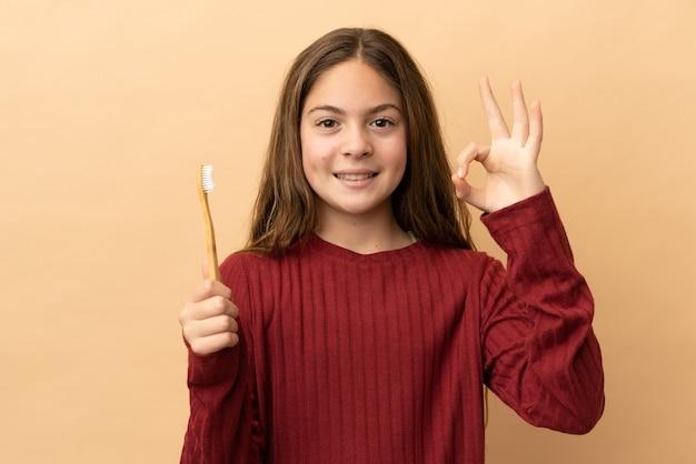 小さな白人の女の子が指でokサインを示すベージュの背景に分離された彼女の歯を磨く