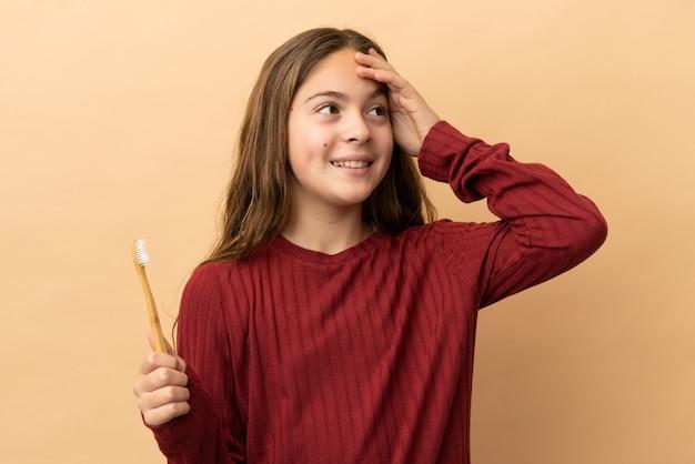たくさん笑ってベージュの背景に分離された彼女の歯を磨く白人の少女