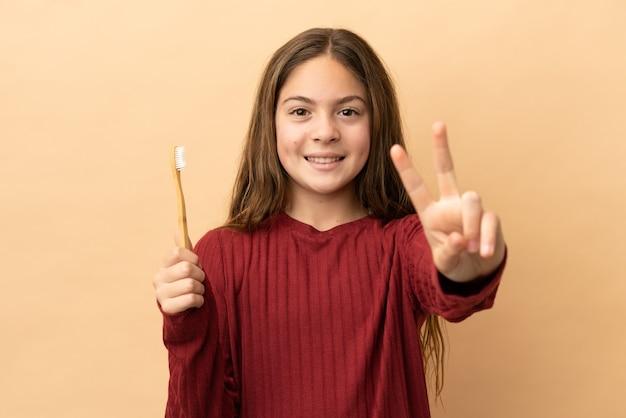 小さな白人の女の子が笑顔で勝利のサインを示すベージュの背景で隔離の彼女の歯を磨く