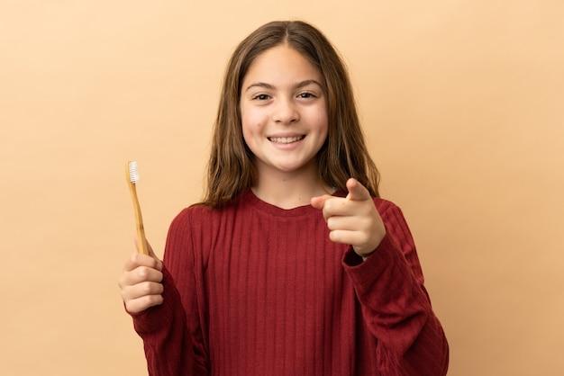 ベージュの背景に分離された彼女の歯を磨く小さな白人の女の子は驚いて正面を指しています