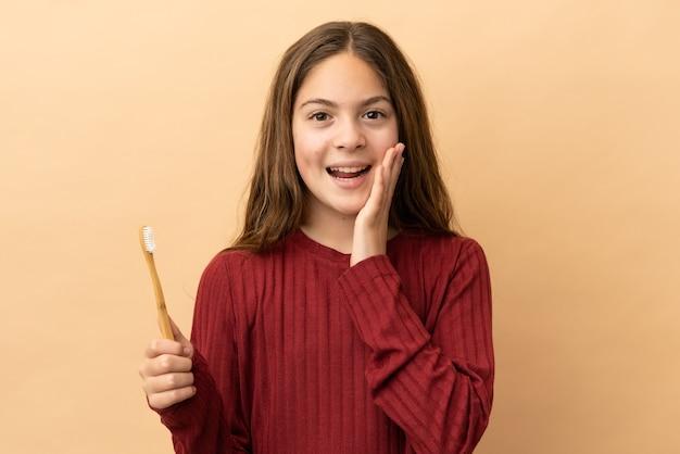 驚きとショックを受けた表情でベージュの背景に分離された彼女の歯を磨く白人の少女