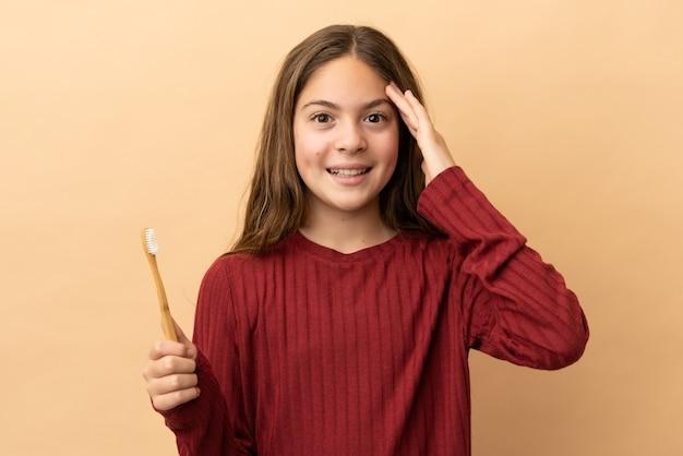 驚きの表情でベージュの背景に分離された彼女の歯を磨く白人の少女