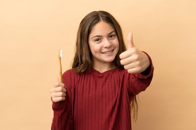 Маленькая кавказская девочка чистит зубы на бежевом фоне с большими пальцами руки вверх, потому что произошло что-то хорошее