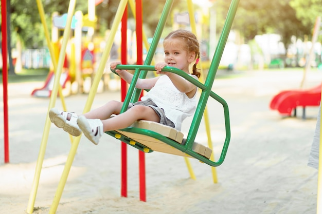 Little caucasian girl child riding on swing on the playground