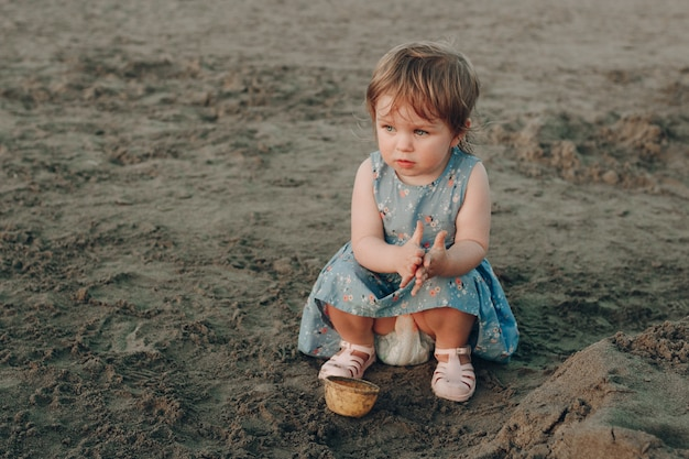 Little caucasian girl have fun digging in the sand at ocean beach, building sand castle.