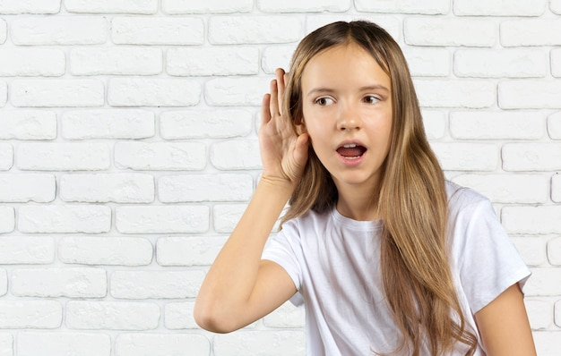 Little caucasian girl in hearing action isolated