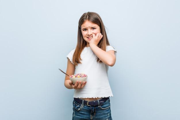 Маленькая кавказская девушка держит миску с хлопьями, кусая ногти, нервная и очень взволнованная.