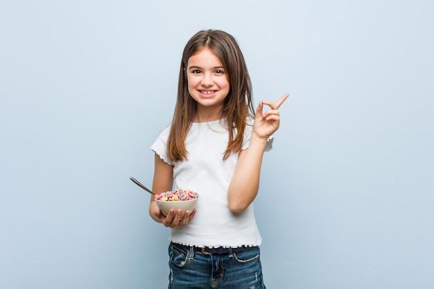 유쾌 하 게 집게 손가락으로 가리키는 웃 고 시리얼 그릇을 들고 어린 있으면 백인 소녀.
