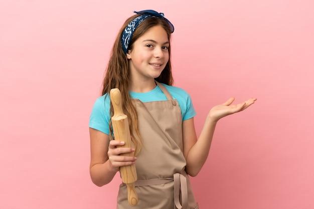 Маленькая кавказская девочка держит скалку на розовом фоне, протягивая руки в сторону, приглашая приехать