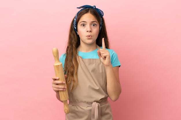 분홍색 배경에 격리된 롤링 핀을 들고 있는 백인 소녀는 손가락을 들어올리면서 솔루션을 실현하려고 합니다.