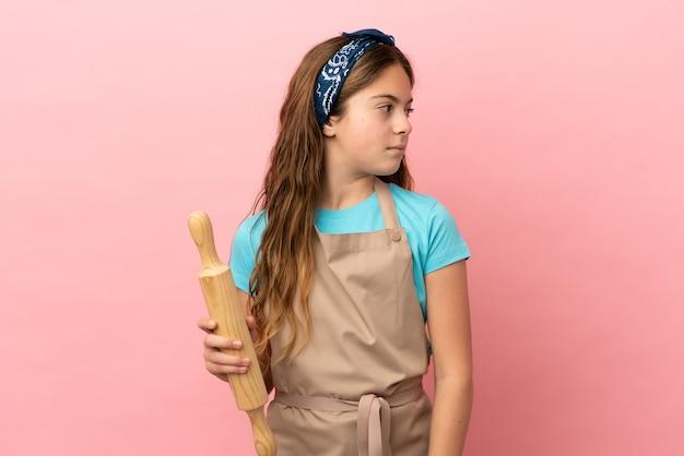 Маленькая кавказская девочка держит скалку на розовом фоне, глядя в сторону