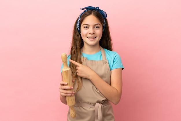 제품을 제시하기 위해 측면을 가리키는 분홍색 배경에 격리된 롤링 핀을 들고 있는 백인 소녀