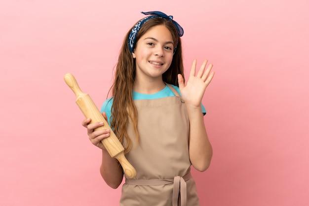 Маленькая кавказская девочка держит скалку на розовом фоне, салютуя рукой с счастливым выражением лица