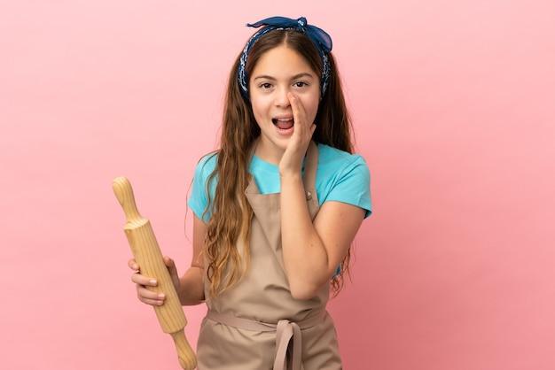 Маленькая кавказская девочка держит скалку на розовом фоне и кричит с широко открытым ртом
