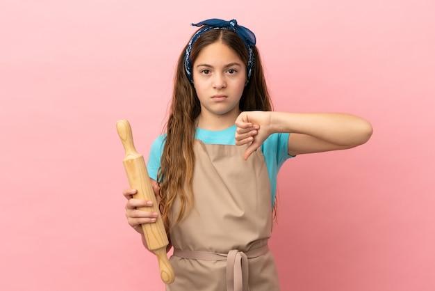 분홍색 배경에 격리된 롤링 핀을 들고 있는 백인 소녀는 부정적인 표정으로 엄지손가락을 아래로 내립니다.