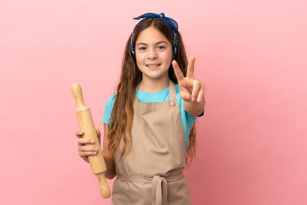 Маленькая кавказская девочка держит скалку, изолированную на розовом фоне, улыбается и показывает знак победы