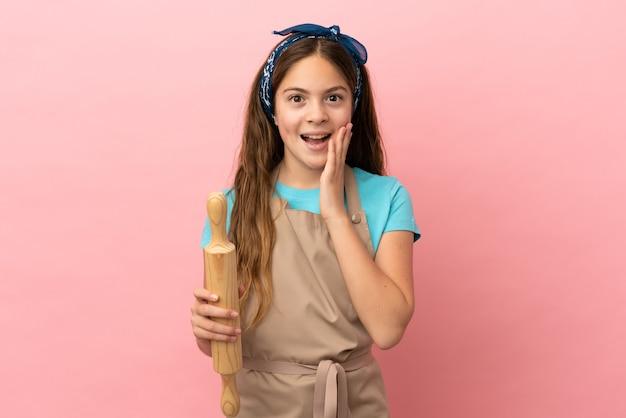 놀라움과 놀란 표정으로 분홍색 배경에 격리된 롤링 핀을 들고 있는 백인 소녀