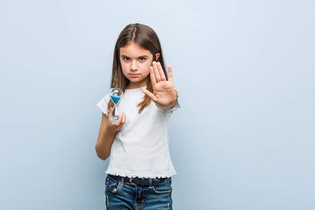Маленькая кавказская девочка держит песочные часы, стоя с протянутой рукой, показывая знак остановки, предотвращая вас.