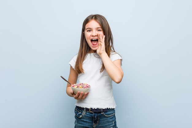 Little caucasian girl holding a cereal bowl shouting excited front.