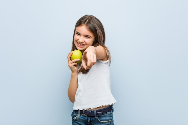 Little caucasian girl holding a green apple cheerful smiles pointing to front.