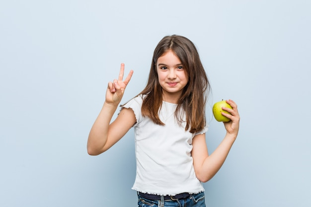 Little caucasian girl holding a green apple showing number two with fingers.