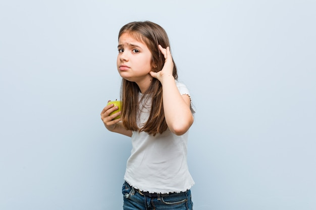 Little caucasian girl holding a green apple trying to listening a gossip.