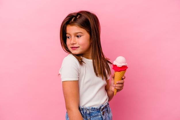 ピンクの背景に分離されたアイスクリームを保持している小さな白人の女の子は、笑顔、陽気で楽しい脇に見えます。