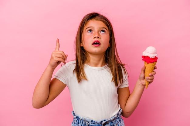 열린 된 입으로 거꾸로 가리키는 분홍색 배경에 고립 된 아이스크림을 들고 어린 백인 소녀.