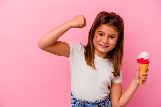 勝利、勝者の概念の後に拳を上げるピンクの背景に分離されたアイスクリームを保持している小さな白人の女の子。