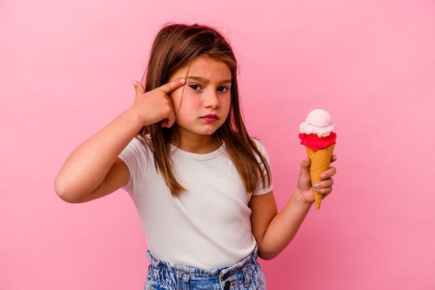 ピンクの背景に分離されたアイスクリームを保持している小さな白人の女の子は、人差し指で失望のジェスチャーを示しています。