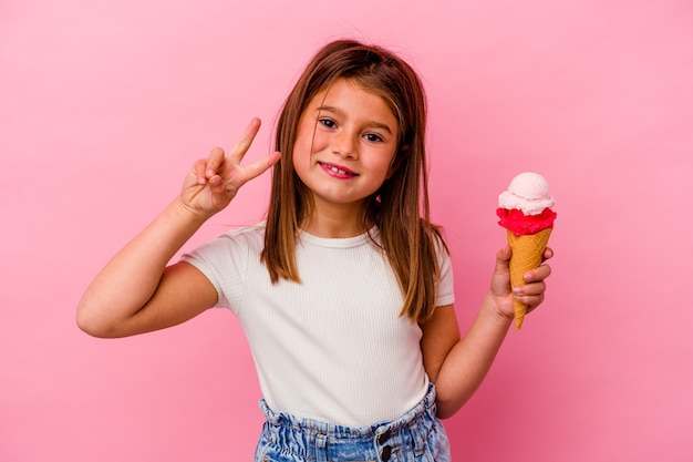 ピンクの背景に分離されたアイスクリームを保持している小さな白人の女の子は、指で2番目を示しています。