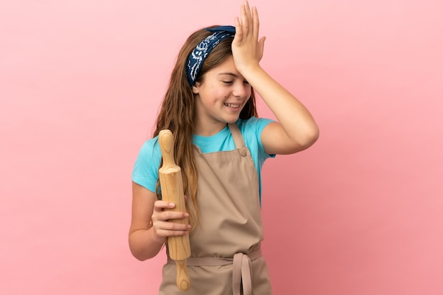 Little caucasian girl holding a rolling pin isolated on pink background has realized something and intending the solution