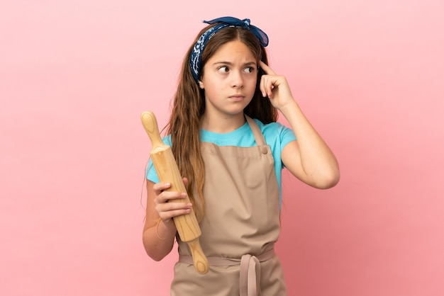 Little caucasian girl holding a rolling pin isolated on pink background having doubts and thinking